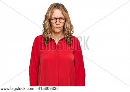 Middle age blonde woman wearing casual shirt over red background skeptic and nervous, frowning upset because of problem. negative person.