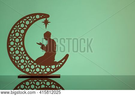 Eid Mubarak Concepts With Crescent Moon In Silhouette With Man Praying.