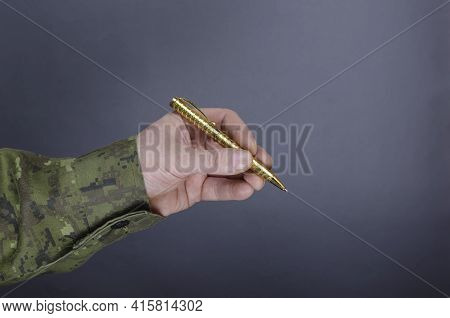 Man In Camouflage Uniform Is Holding Pen Against Gray Background. Middle-aged Man's Hand With A Gold