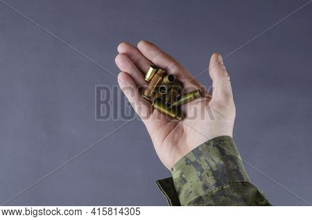 Empty Casings In A Man's Hand Against A Gray Background. A Man In A Camouflage Uniform Is Holding Pi