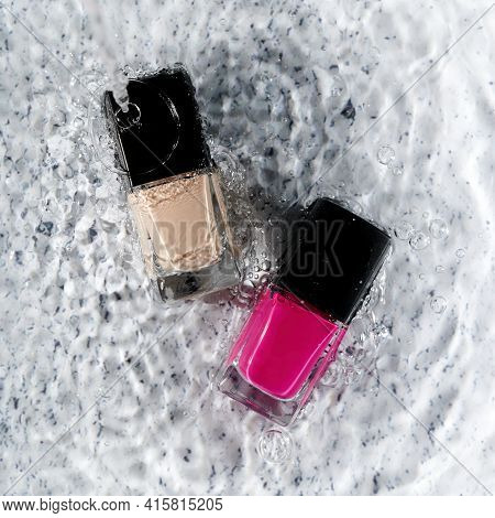 Nail Polishes Immersed In Water On A Light Background. Top View.