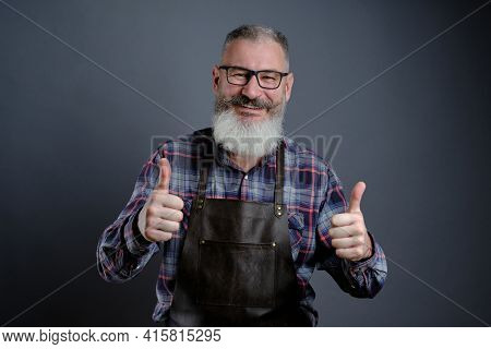 Portrait Of Handsome Mature Bearded Man Dressed Leather Apron Gesturing Thumbs Up Over Gray Backgrou