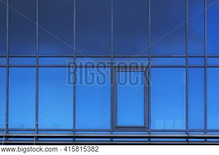 Windows on facade of modern building. Reflection of sky in windows glass. Abstract architectural blue background.