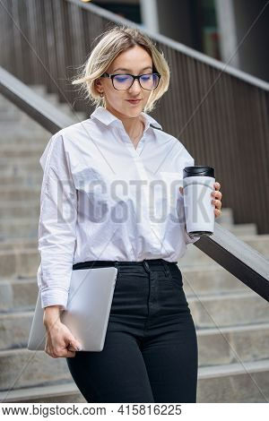 A Business Woman In A White Shirt And Black Trousers Descends The Stairs. Young Blond Woman With Cof
