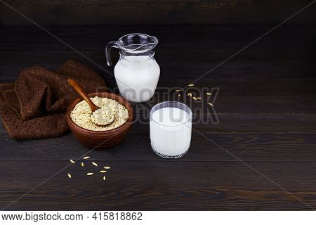 Oatmeal Milk In A Jug And A Glass, Oatmeal Flakes In A Ceramic Bowl On A Dark Wooden Background. Veg