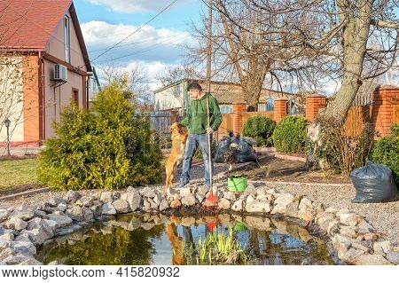 Mature Caucasian Man With His Dog Cleans A Garden Pond From Water Plants And Falling Leaves. Spring