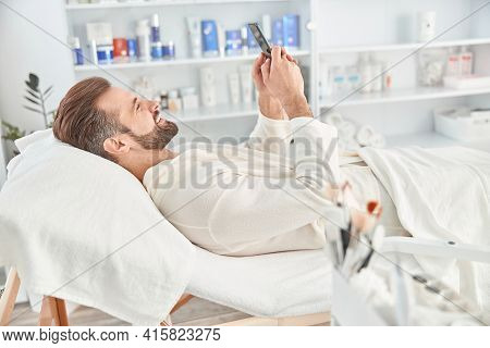 Young Man Smiling And Holding Smartphone While Waiting For Cosmetic Procedure In Clinic Of Esthetic