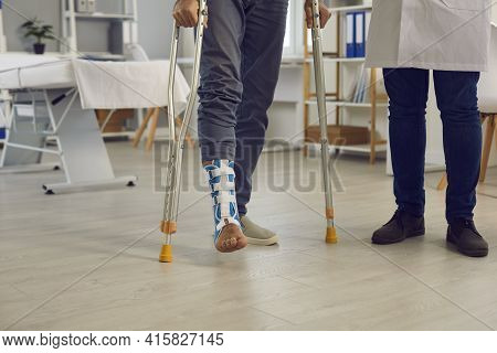 Midsection Of Patient With Injured Leg Walk With Crutches Under Doctor Control