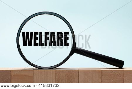 Cubes On A Light Blue Wooden Background. On Them A Magnifying Glass With The Word Welfare