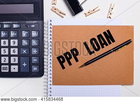On The Desktop Is A Calculator, A Pen And Clothespins Near A Notebook With The Text Ppp Loan. Busine