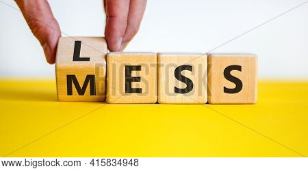 Less Mess Symbol. Businessman Turns The Cube And Changes The Word 'mess' To 'less'. Beautiful Yellow