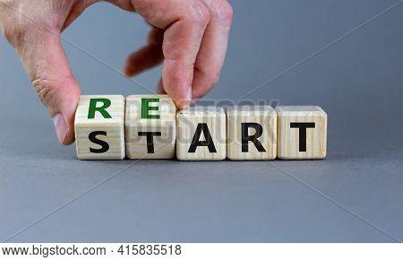 Restart Symbol. Concept Word 'restart' On Wooden Cubes On A Beautiful Grey Table. Businessman Hand.