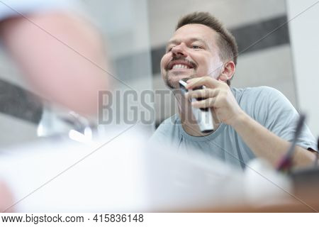 Man Shaves His Stubble With Machine In Front Of Mirror