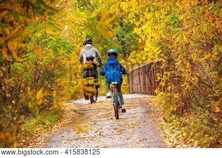 Family Cycling In Golden Autumn Park, Active Father And Kids Ride Bikes, Family Sport And Fitness Wi