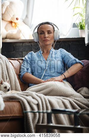 Leisure time concept. Happy beautiful woman listening to the music using headphones sitting on a couch indoors. Female spending her free day and relaxing at home alone with dog on her laps.