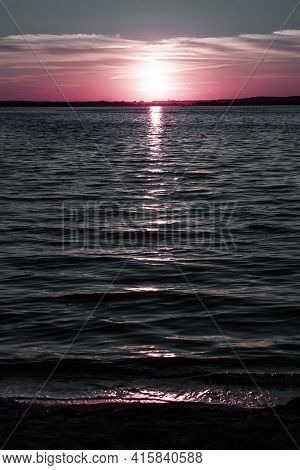 Vertical Enigmatic Seascape Picture With Dreamy Pink Sunset Over The Dark Sea Water At Calm Evening