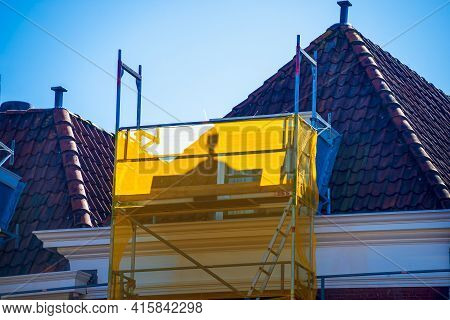 Scaffold At The Construction Site With Yellow Plastic Foil, Leiden, Netherlands