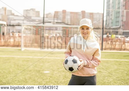 Pretty Womens Soccer. Young Woman In Sportswear With A Soccer Ball On The Grass