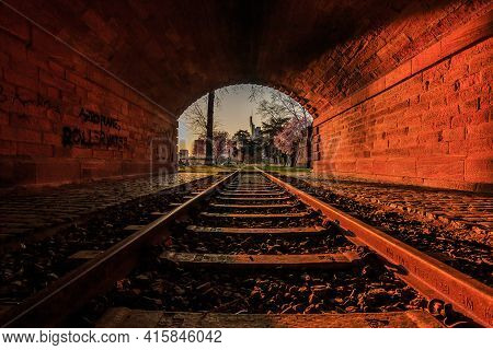 Old Tunnel With Railroad Track In The Evening At Sunset. Frankfurt Skyline At The Tunnel Exit. Park