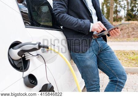 Business Man Standing Near Charging Electric Car Or Ev Car And Using Tablet In The Street.