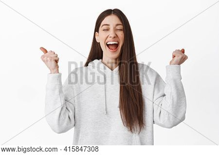 Relieved And Happy Girl Scream From Excitement And Joy, Shaking Hands With Closed Eyes And Laughing,