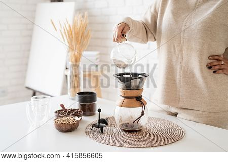 Young Woman Brewing Coffee In Coffee Pot, Pouring Hot Water Into The Filter