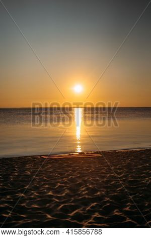 Dawn At Sea. A Yoga Mat Lies On The Sand. Bright Orange Sky And Water Reflection. Vertical Photo
