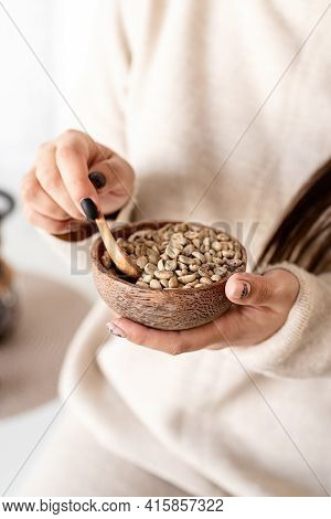 Woman Hand Holding Bowl With Green Coffee Beans
