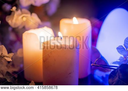 Zoomed In Shot Of Large Thick Wax Candles With Flames Lit And Colorful Flowers All Round And Led Lig