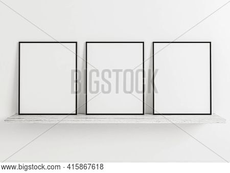 Triple 8x10 Vertical Black Frame Mockup On Wooden Shelf And White Wooden Wall. Three Empty Poster Fr
