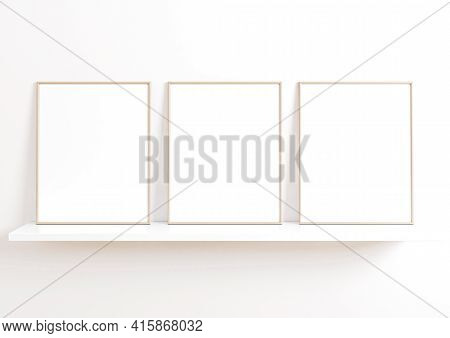 Triple 8x10 Vertical Beige Frame Mockup On White Shelf And White Wall. Three Empty Poster Frame Mock