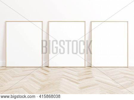Triple 8x10 Vertical Beige Frame Mockup On Wooden Floor And White Wall. Three Empty Poster Frame Moc
