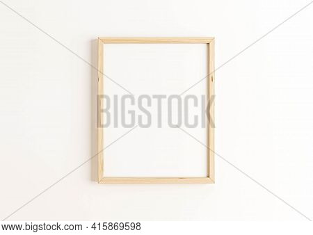 Single 8x10 Vertical Wooden Frame Mockup On White Wall. One Empty Poster Frame Mockup On White Backg