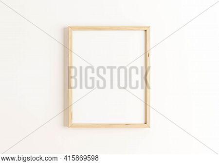 Single 8x10 Vertical Wooden Frame Mockup On White Wall. One Empty Poster Frame Mockup On White Backg