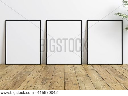 Triple 8x10 Vertical Black Frame Mockup On Wooden Floor And White Wall. Three Empty Poster Frame Moc