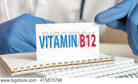 Doctor Holding A White Paper Card With Text: Vitamin B12. Healthcare Conceptual For Hospital, Clinic
