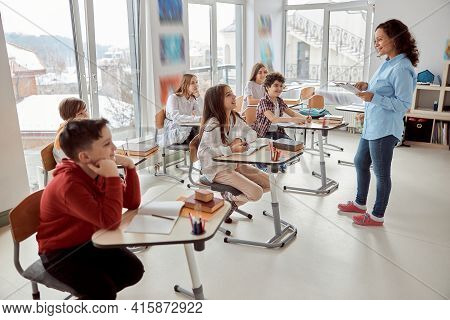 Cheerful And Happy Children Sitting At Desk While Teacher Speaking In School Classroom. Elementary S