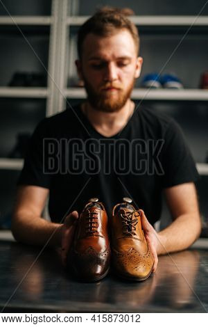 Portrait Of Male Shoemaker Holds Old Light Brown Leather Shoe And Repaired Shiny Shoes After Restora