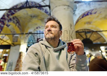 Mature Man Drink Turkish Tea Sitting In Small Cafe In The Grand Bazaar In Istanbul, Turkey. Dishes O