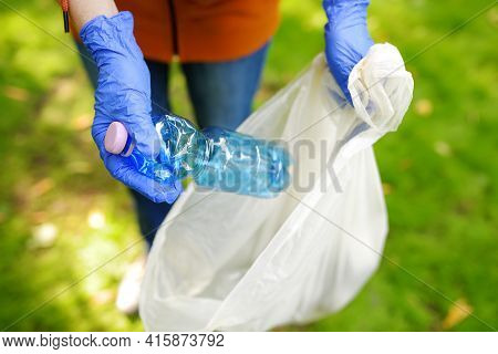 Volunteer Picking Up The Plastic Garbage And Putting It In Biodegradable Trash-bag On Outdoors. Ecol