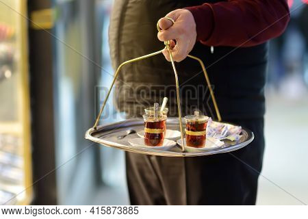 The Waiter Of Outdoors Cafe Is Serving Tray With Glasses Of Traditional Turkish Tea. Grand Bazaar, I