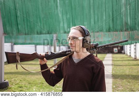 A Man In Protective Glasses And Headphones. A Pump-action Firearm Shotgun. Tyre's Outdoors. Green Gr
