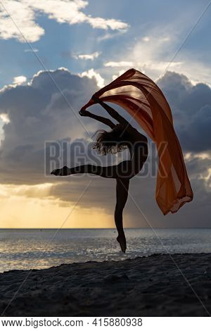 Flexible Fit Woman Jumping With Silk During Dramatic Sunset With Stormy Clouds. Concept Of Aspiratio