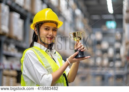 Happy Smiling Woman Warehouse Staff Holding A Trophy After Being Selected As An Outstanding Employee