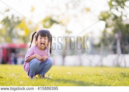 Happy Child Laughed Brightly. Children Squatting In Middle Of Lawn. Kid Sticks Out His Tongue Making