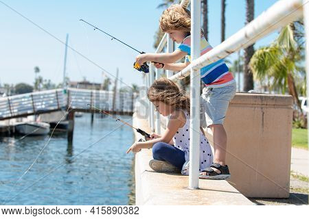Couple Of Kids Fishing On Pier. Child At Jetty With Rod. Boy And Girl With Fish-rod