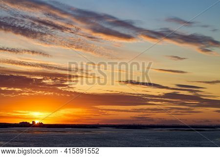 Sunset On The River. Colorful Landscape With River And Blue Sky With Multicolored Clouds. River Suns