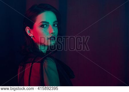 Portrait of a beautiful brunette young woman in a luxury apartment in in mixed lighting. Beauty, fashion concept. Glamorous lifestyle.