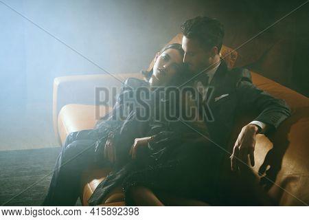Beautiful elegant couple in fashionable evening clothes posing in haze in  luxury apartment. Glamorous lifestyle. Fashion shot.