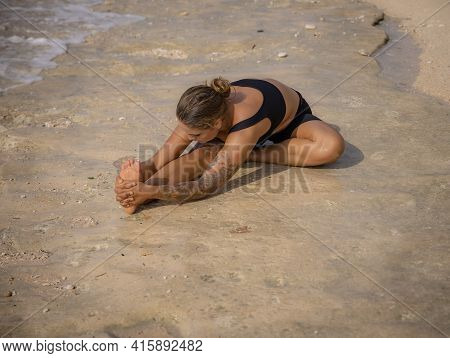 Beach Yoga. Woman Practicing Janu Shirasasana Or Head-to-knee Pose. One-legged Forward Bend. Seated